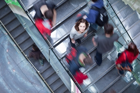 At the universitycollege - Students rushing up and down a busy stairway - confident pretty young female student looking upwards (color toned image) photo