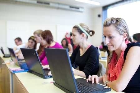 higher learning: college students sitting in a classroom, using laptop computers during class (shallow DOF)