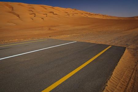 empedrado: La modernidad frente al concepto de la naturaleza - fin de la civilización, a partir del desierto. Carretera pavimentada moderna que termina en las dunas de arena. Foto de archivo