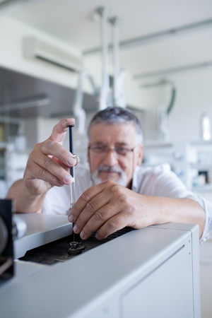 chromatograph: senior male researcher carrying out scientific research in a lab using a gas chromatograph (shallow DOF; color toned image)