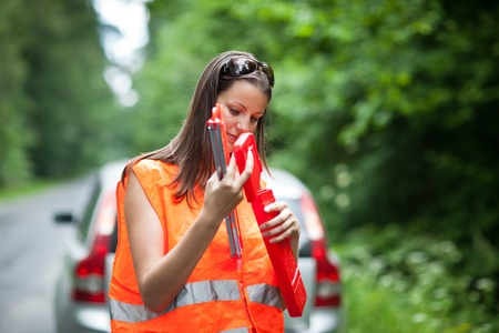 warning triangle: Young female driver wearing a high visibility vestsafety vest, putting in place the warning triangle after her car has broken down Stock Photo