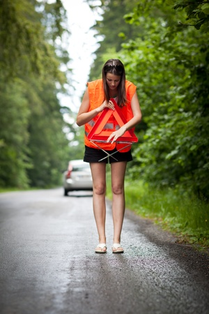 Young female driver wearing a high visibility vest/safety vest, putting in place the warning triangle after her car has broken down Stock Photo - 10409980