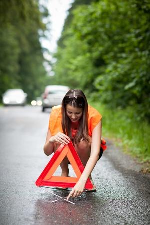 zichtbaarheid: Jonge vrouwelijke chauffeur het dragen van een hoge zichtbaarheid vest  veiligheidsvest, de invoering van de gevarendriehoek nadat haar auto heeft afgebroken
