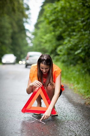 emergency call: Young female driver wearing a high visibility vestsafety vest, putting in place the warning triangle after her car has broken down Stock Photo