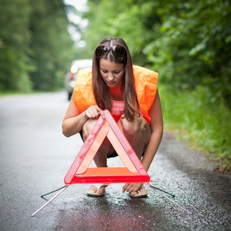 Young female driver wearing a high visibility vest/safety vest, putting in place the warning triangle after her car has broken down Stock Photo - 10409928