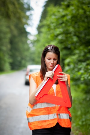 Young female driver wearing a high visibility vest/safety vest, putting in place the warning triangle after her car has broken down Stock Photo - 10409929