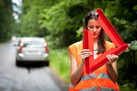 stopped: Young female driver wearing a high visibility vestsafety vest, putting in place the warning triangle after her car has broken down Stock Photo
