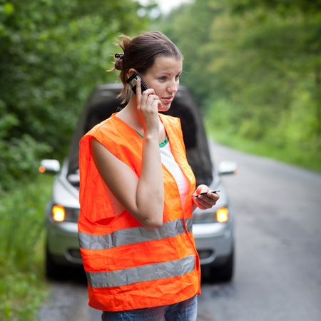 emergency call: Young female driver wearing a high visibility vest, calling the roadside serviceassistance after her car has broken down Stock Photo