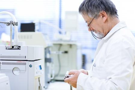 investigador cientifico: investigador senior masculino llevar a cabo la investigaci�n cient�fica en un laboratorio (DOF, imagen en color entonado) Foto de archivo