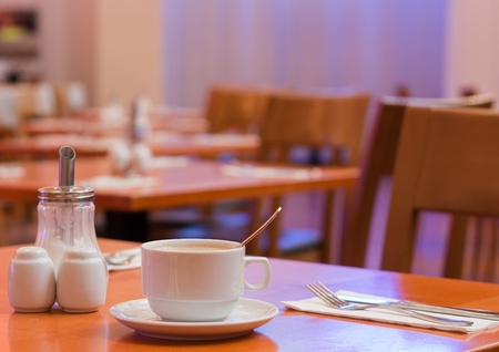 Close up of a cup of coffee on a table set for breakfast in a hotel cafe/restaurant/dining hall Stock Photo - 10467342