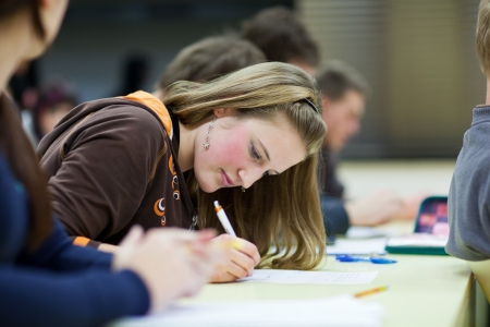 school exam: pretty female college student sitting in a classroom full of students during class (shallow DOF; color toned image) Stock Photo