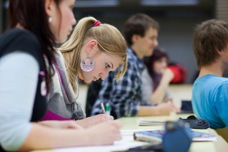 Teenagers studying: estudiante bastante femenina sentada en un aula lleno de estudiantes en la clase (DOF superficial; imagen de tonos de color)