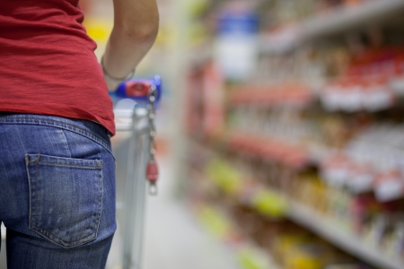 gastos: Young woman shopping for groceries in a supermarket Imagens