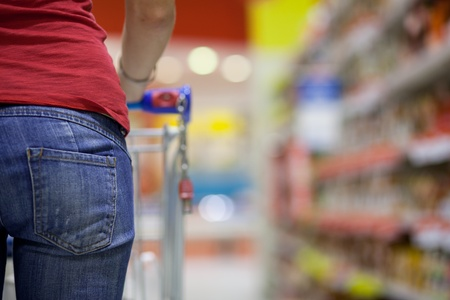 aisle: Young woman shopping for groceries in a supermarket Stock Photo