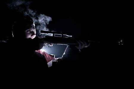 hombre disparando: joven disparos con un rifle (tonos de color de imagen)
