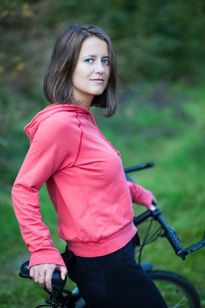 pretty young female biker outddors on her mountain bike (shallow DOF; selective focus) photo