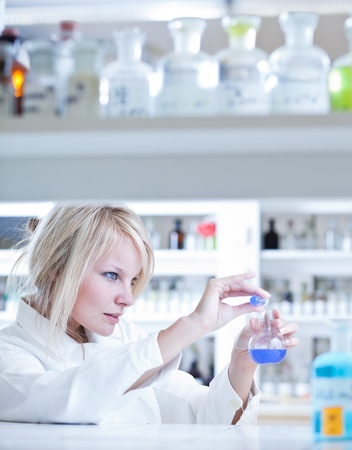 Closeup of a female researcher holding up a test tube and a retort and carrying out experiments Stock Photo - 10523625