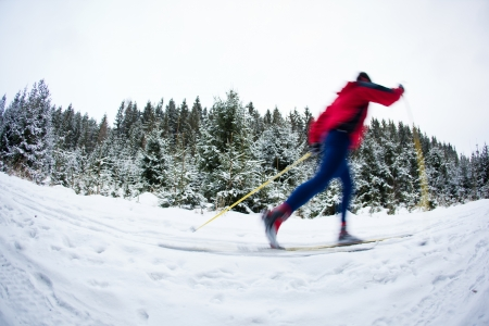 young man cross-country skiing on a snowy forest trail (color toned image)