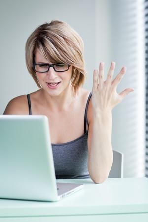 molesto: joven empresaria mostrando molestia sobre un problema mientras trabajaba en su computadora portátil (tonos de color de imagen)