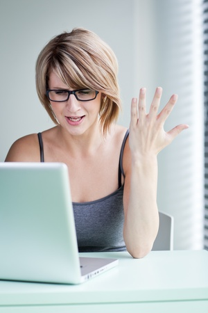young businesswoman showing annoyance over a problem while working on her laptop (color toned image) Stock Photo - 10523641