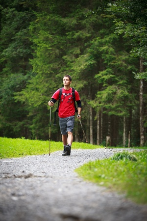 active handsome young man nordic walkinghiking in mountains, enjoying the outdoors photo