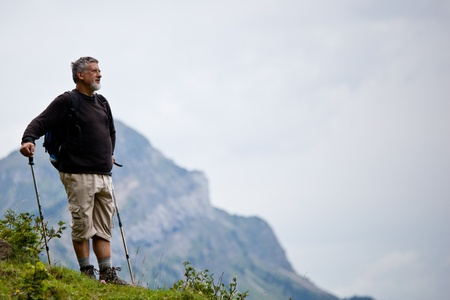active handsome senior man nordic walking outdoors on a forest path, enjoying his retirement Stock Photo - 10575827