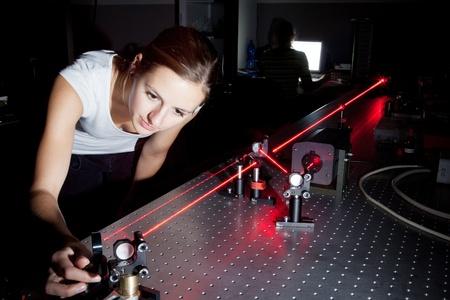 experimento: científico de las mujeres haciendo la investigación en un laboratorio de óptica cuántica Foto de archivo