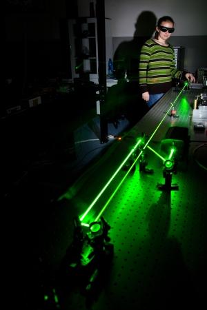 quantum physics: female scientist doing research in a quantum optics lab
