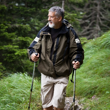 active handsome senior man nordic walking outdoors on a forest path, enjoying his retirement Stock Photo - 10575566