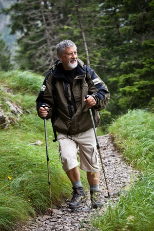 active handsome senior man nordic walking outdoors on a forest path, enjoying his retirement photo
