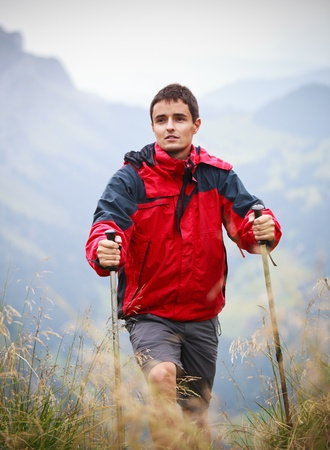 action fund: active handsome young man nordic walkinghiking in mountains, enjoying the outdoors