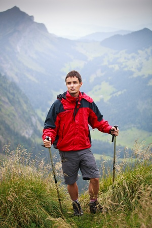 active handsome young man nordic walking/hiking in mountains, enjoying the outdoors Stock Photo - 10575932