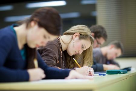 mooie vrouwelijke student zit in een klas vol leerlingen tijdens de les Stockfoto