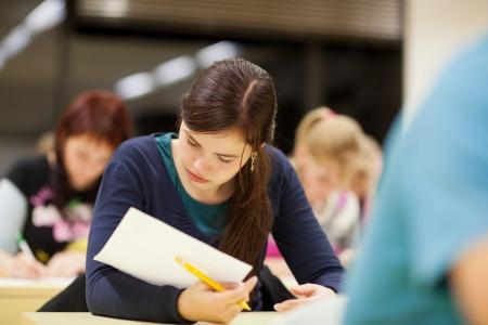 꽤 여성 대학 학생 수업 중 학생들의 전체 교실에 앉아 (얕은 DOF, 톤 컬러 이미지)