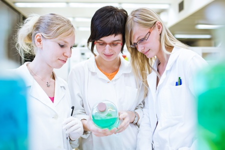 three researcherschemistry students carrying out research in a chemistry lab (color toned image; shallow DOF) photo