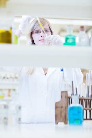 lab technician: portrait of a female researcher carrying out research in a chemistry lab (color toned image; shallow DOF)