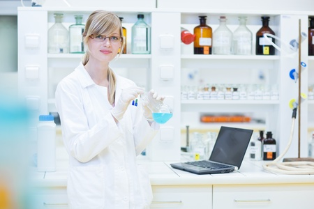 laboratory coat: portrait of a female researcher carrying out research in a chemistry lab (color toned image; shallow DOF)