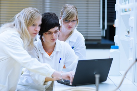 experiment: female researchers carrying out research together in a chemistry labresearch center (color toned image; shallow DOF)