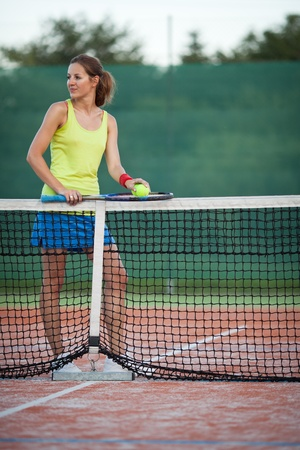 pretty young female tennis player on a tennis court (shallow DOF, selective focus) photo