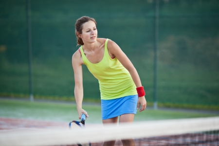 tennis racquet: pretty young female tennis player on a tennis court (shallow DOF, selective focus)