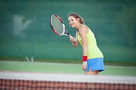 jugando tenis: tenista bastante joven en una cancha de tenis (DOF superficial, enfoque selectivo) Foto de archivo