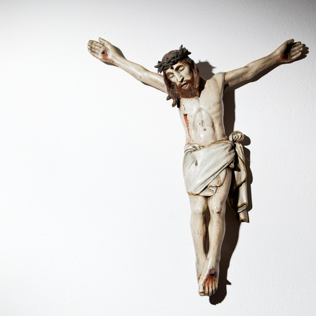 crucifix: Very old carved and painted wooden crucifix on a wall in a historical country cottage Stock Photo