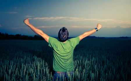 arms raised: Young man enjoying his freedomrejoicing from his success in the countryside, in a wheat field at dusk (color toned image) Stock Photo