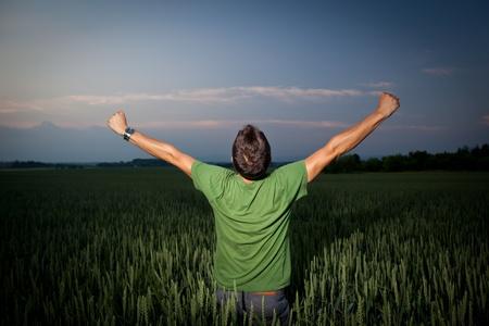 manos levantadas al cielo: Joven disfrutando de su libertad  alegr�a de su �xito en el campo, en un campo de trigo al atardecer Foto de archivo