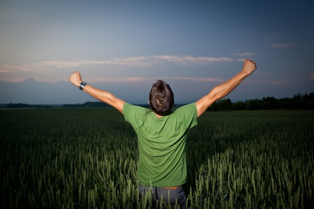 arms outstretched: Young man enjoying his freedomrejoicing from his success in the countryside, in a wheat field at dusk