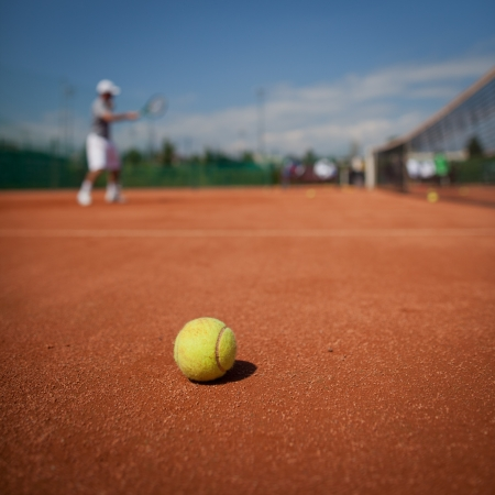 tenis: Jugador de tenis en la acción en la cancha de tenis (enfoque selectivo, centrarse en la pelota en primer plano)