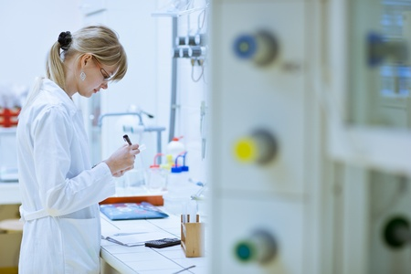 female researcher carrying out research experiments in a chemistry lab (color toned image) Stock Photo