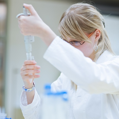 laboratory technician: Closeup of a female researcher carrying out research experiments in a chemistry lab (color toned image) Stock Photo
