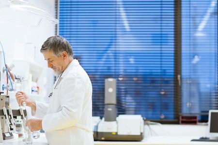 experimento: investigador senior masculina llevar a cabo la investigaci�n cient�fica en el laboratorio utilizando un cromat�grafo de gases (DOF bajo; imagen de tonos de color)