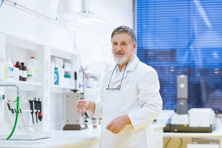 bata de laboratorio: investigador senior masculino llevar a cabo la investigaci�n cient�fica en el laboratorio utilizando un cromat�grafo de gases (DOF, imagen en color entonado) Foto de archivo